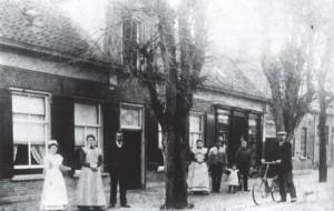 Rechts is nog een gedeelte van de slachterij van Kohen te zien naast de smederij van de famie Koops, die voor de smederij staat. De man met de fiets is dhr. Bosch, de gemeenteontvanger.